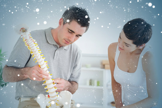 Chiropractor and patient looking at a model of a spine against snow