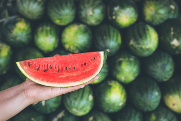 Hands holding piece of fresh red slice watermelon on the heap background