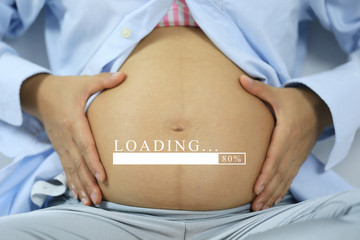 Belly of pregnant women and loading text in concept of time in childbirth.