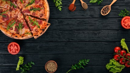 Pizza with sausage salami and mozzarella. Top view. On a wooden background. Copy space.