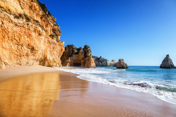 Wall Mural - beautiful sea view with secret sandy beach among rocks and cliffs in Algarve, Portugal