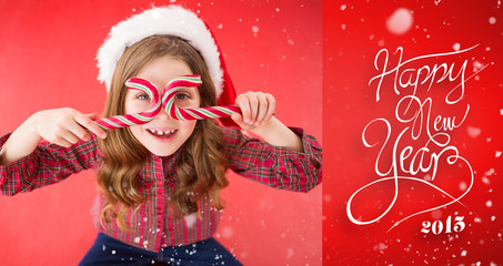 Happy little girl in santa hat holding candy canes against red vignette