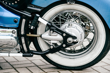 Motorcycle wheel with disk brakes system and metal spokes. Closeup detailed photo of motorbike forks and tire. Different parts of two-wheeled vehicle.  Transportation. Modern driving technologies.