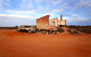 Crumbling stone home and rusty car