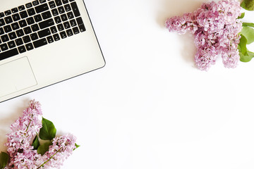 Cropped image of laptop keyboard & lilac flowers in minimal arrangement on white table top background. Feminine flat lay composition with pc notebook computer and purple bouquet. Close up, copy space.