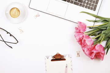 Feminine desktop, close up of laptop keyboard, blank clipboard, coffee, tulip flowers, eyewear. Flat lay composition, notebook computer, cappuccino cup, glasses eye wear, white background. Copy space.