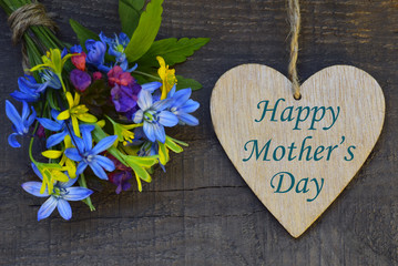 Happy Mother's Day greeting card with spring flowers bouquet and decorative heart on old wooden background. Selective focus.