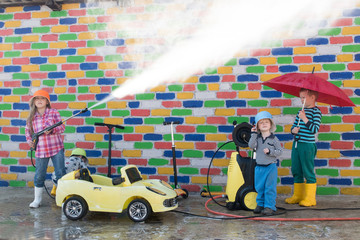Happy girl with children washes yellow toy car from high pressure washer in front of a multi-colored brick wall. Fun during the summer holidays. The concept of family business.
