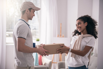 Professional delivery service. Positive friendly man looking at the woman while giving her the package