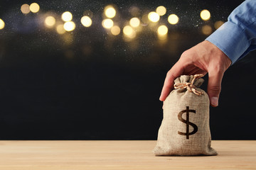 Male hand holding a sack of money over wooden desk and glitter black background.
