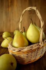 Little pears in a wicker basket on wooden background