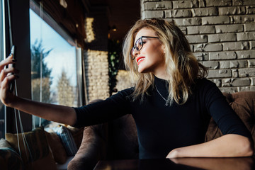 Young beautiful blonde woman taking a selfie in coffee shop. Hipster, red lips, glasses.