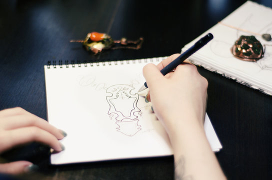 Artist designer girl draws sketch of unusual jewelry ornaments with a pen on white paper. Home workshop