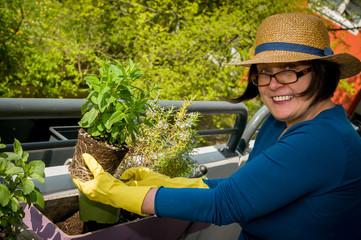 Eine Frau mittleren Alters pflanzt Kräuter und Blumen auf dem Balkon