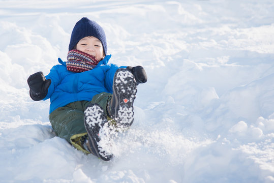 Asian child sliding on snow