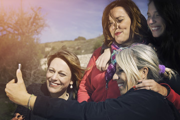 Four women friends are doing a selfie. Nature background.