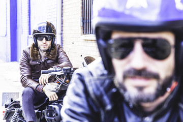 Modern bikers sits on classic motorcycle ready for photo shooting. Outdoor portrait and urban lifestyle