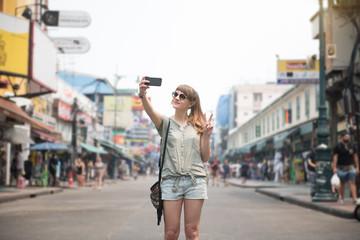 Woman taking selfie on road