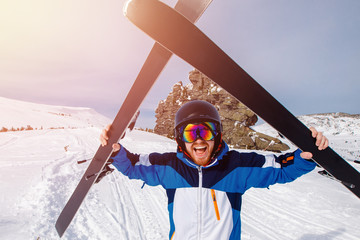Selfie Guy sportsman goes on normal skiing on ski slope with action camera.