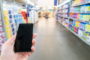 Hand with mobile phone on a background of a blurry shopping center
