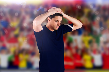 Disappointed football player looking down against blurry football pitch with crowd