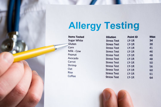 Analysis and testing for allergies photo concept. Doctor points with pen in his hand on result of patient allergy test in foreground, standing in medical gown with stethoscope in blurred background