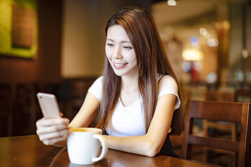 young woman using smart phone in coffee shop