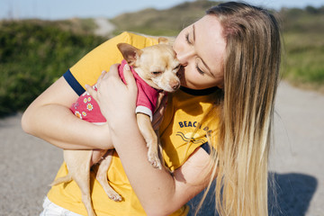 Girl kissing small Chihuahua in sunlight