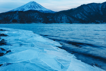 Mt. Fuji looms behind a half frozen lake.