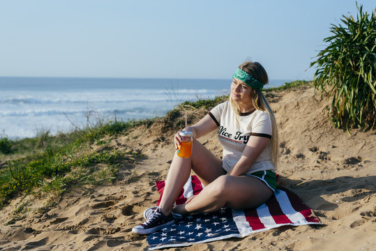 Casual girl with drink on sand