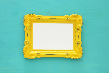 Vintage blank yellow photo frame over mint background. Ready for photography montage. Top view from above.