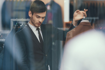 Successful young businessman looks at jacket in business mens clothing store.