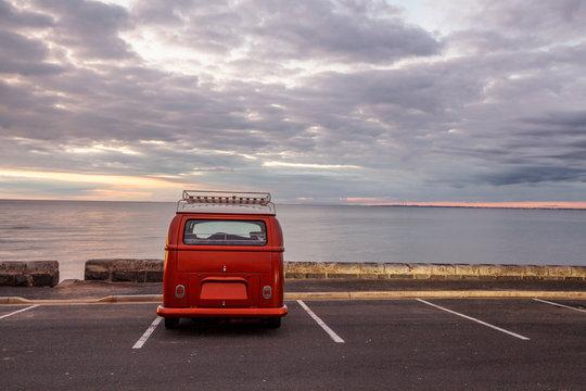 Vintage minivan on empty parking lot at the beach at sunset