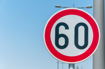 Traffic speed limit sign for restriction on 60 kilometers or miles per hour with blue sky background