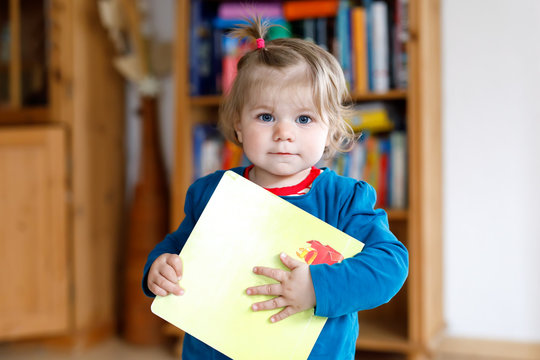 Adorable baby girl holding a book. Beautiful toddler child at home wants reading fairy tale.
