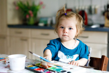 Cute adorable baby girl learning painting with water colors. Little toddler child drawing at home, using colorful brushes