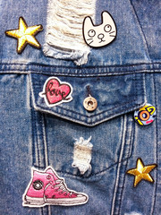 Vintage denim texture background: jacket close-up with pocket and colorful decor. Patches, embroidery, badge.