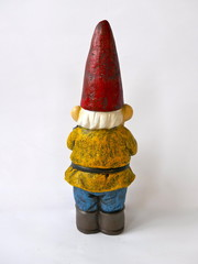 Gartenzwerg von hinten  mit rotem Hut, gelber Jacke, blauer Hose und  braunen Stiefeln