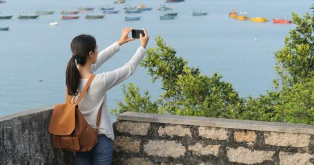 Woman taking photo on the sea
