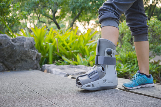 Female patients wear shoes designed specifically for ankle sprain or diabetes. To exercise by walking in the park. On the advice of an orthopedic doctor. medical and healthcare concept.