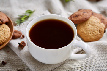 Coffee cup, jar with coffee beans, cookies over homespun tablecloth, selective focus, close-up, top view