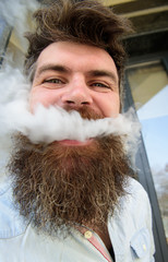 Hipster with tousled hair and gray on relaxed cheerful face with white smoke flying out of mouth. Vaping concept. Man with beard and mustache smoking, building background.