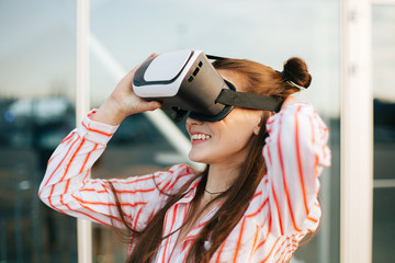 Beautiful fashion model with long hair plays a VR-game standing before glass building outside