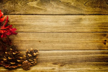 Three small pine cones with a wood background providing copy space