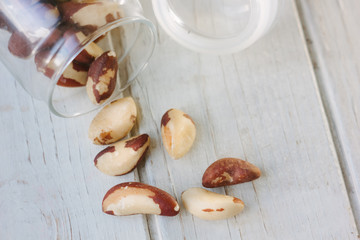 Brazil nuts and glass bottle over the white table
