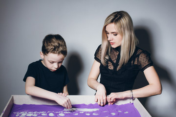 Woman and a boy draw on an interactive sand table