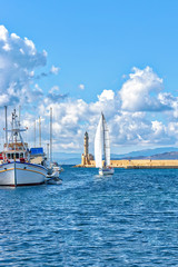Yacht on background of Lighthouse in the Old Venetian Harbour in Chania . Crete. Greece.
