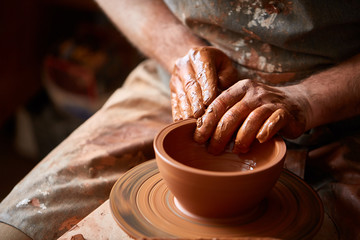 Close-up hands of a male potter in apron molds bowl from clay, selective focus Fototapete