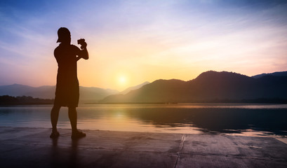 Man traveler taking photos of sunset at mountain and river landscape.