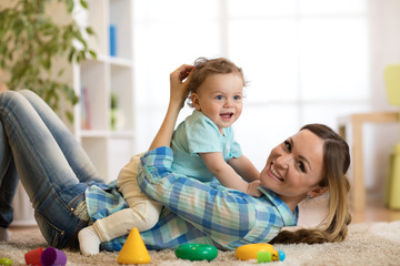 Happy mother and baby son lying on the floor and playing indoor